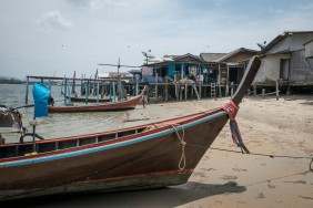Long-tail boats pulled up alongside the riverside houses, Saladan.